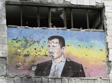 File photo of mural of Syria's President Assad riddled with holes on the facade of the police academy in Aleppo after it was captured by Free Syrian Army fighters